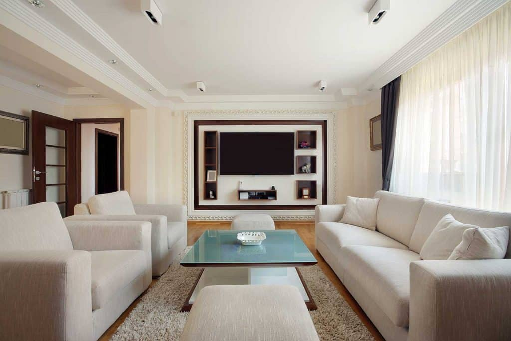 Living room interior with sofa set, coffee table on carpet rug and white curtain on glass window
