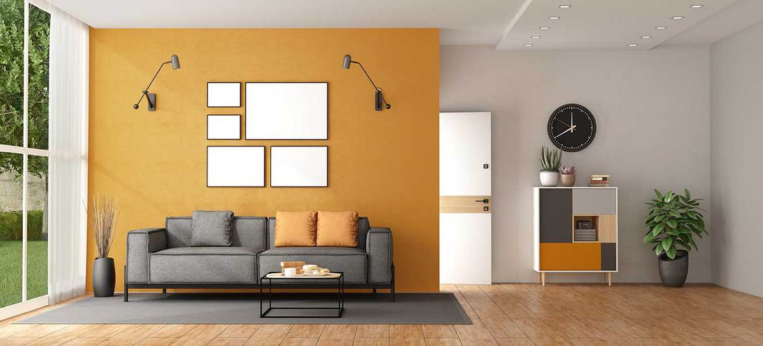 Living room of a modern villa with gray sofa against orange wall and front door on background