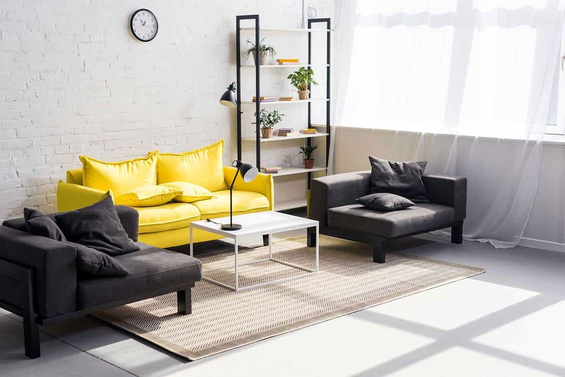 Living room with black and yellow sofa, carpet on floor and wall clock on brick wall