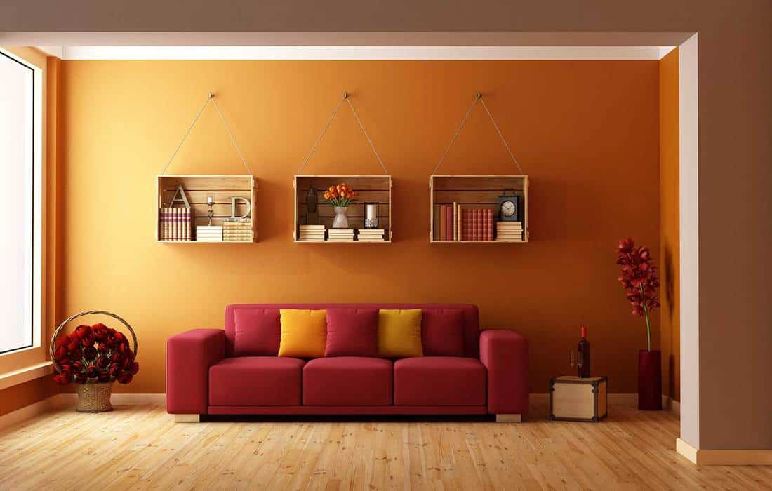 Living room with red sofa and wooden crates used as a bookcase