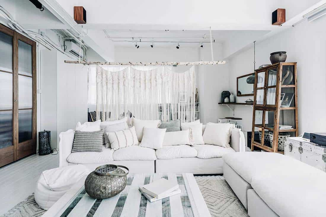 Loft living room interior with cozy white sofas and throw pillows