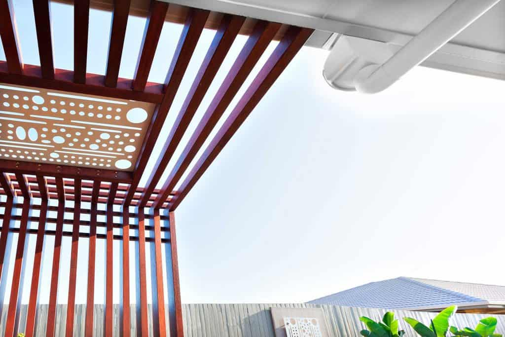 Low angle view of wooden pillars and beams with a white carving