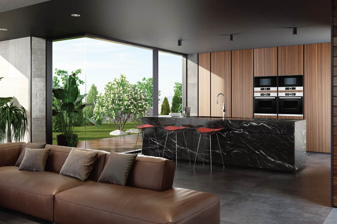 Luxurious living room and kitchen with black granite kitchen island, red stools, dark gray floor, and brown wooden kitchen cabinets
