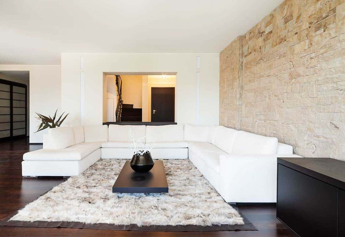 Luxury living room with large white sofa, cozy carpet rug and stylish brick wall
