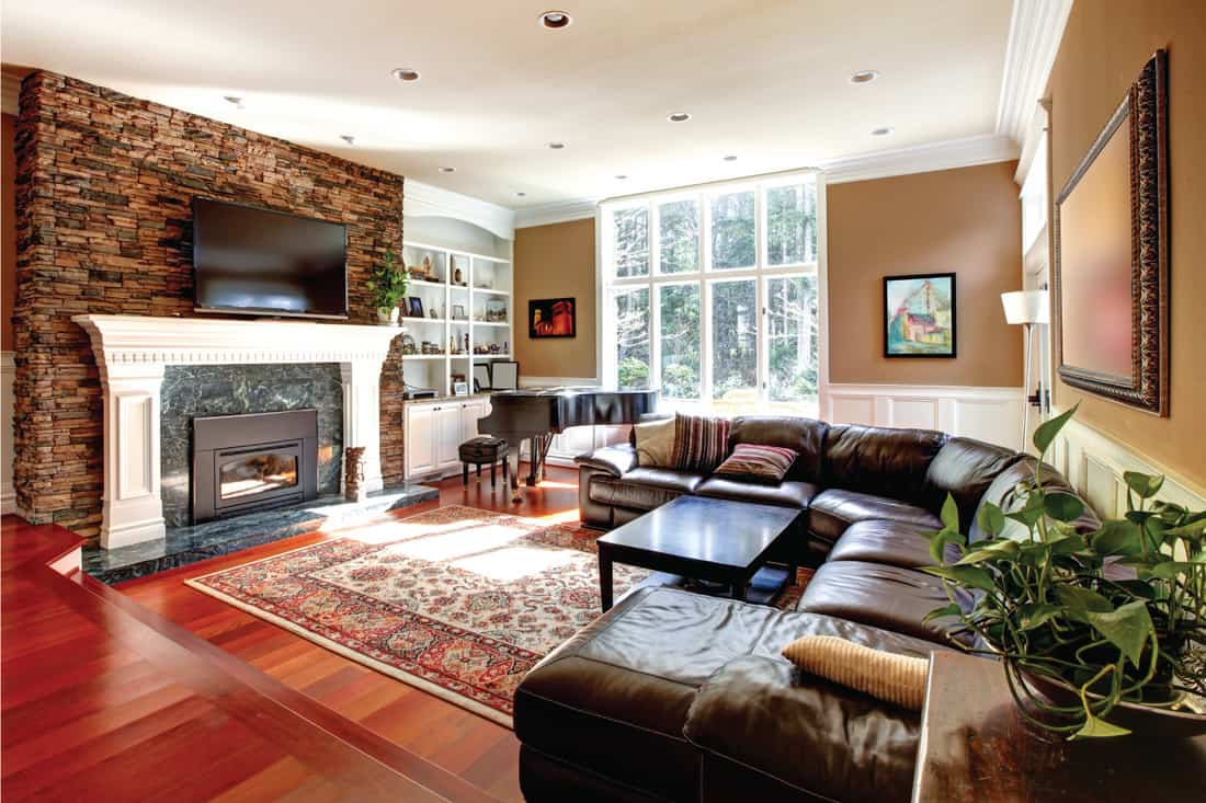 Luxury living room with stobe fireplace and leather sofas. warm and cozy living room