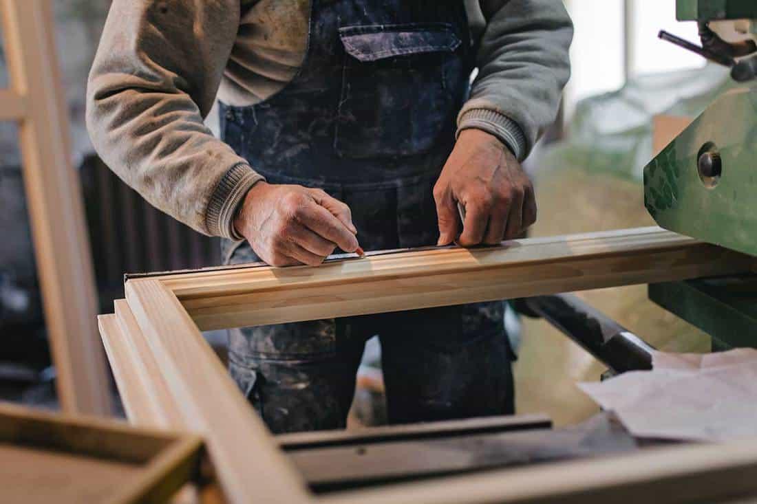 Mature carpenter measuring window frame in the workshop