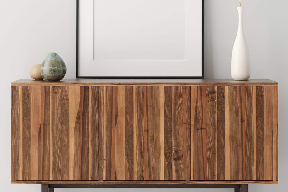 Mock up poster frame on wooden teak furniture cabinet in home interiorShould You Oil Teak Furniture?
