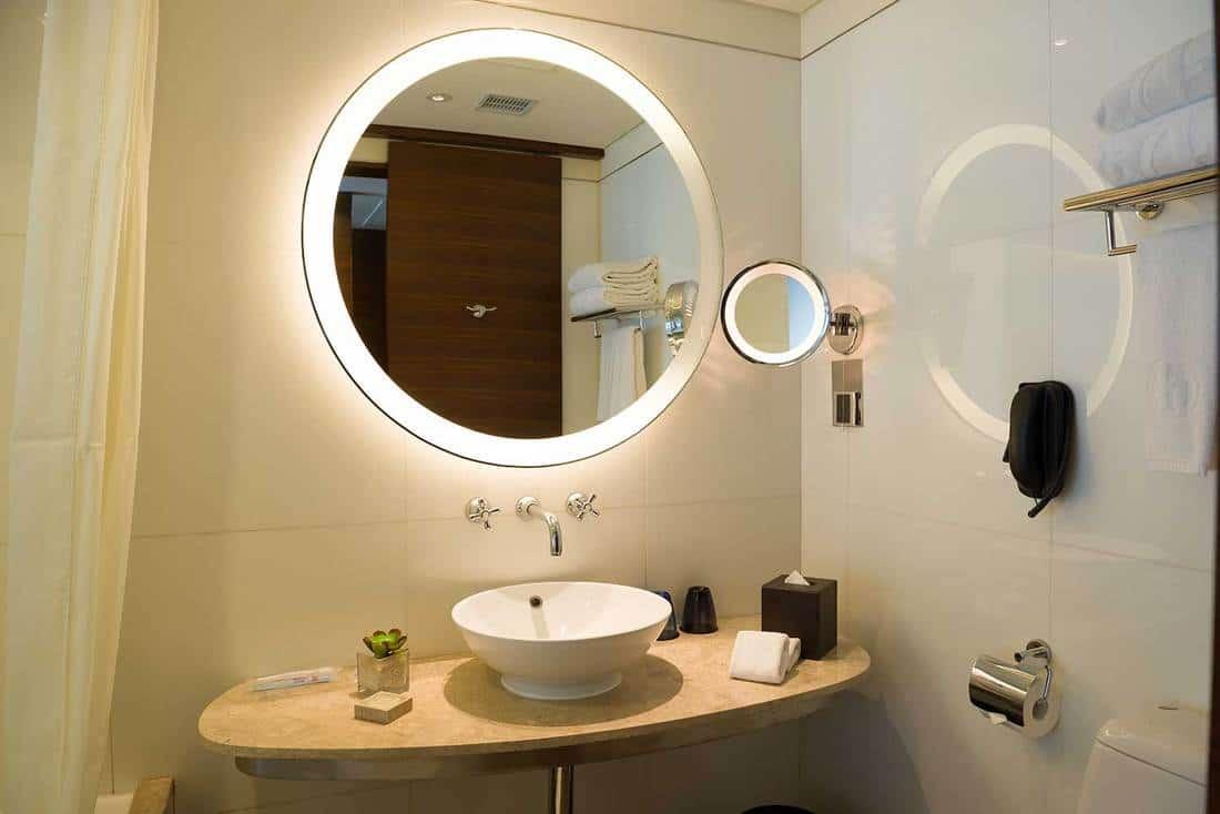 Modern bathroom interior with luxury round mirror above sink