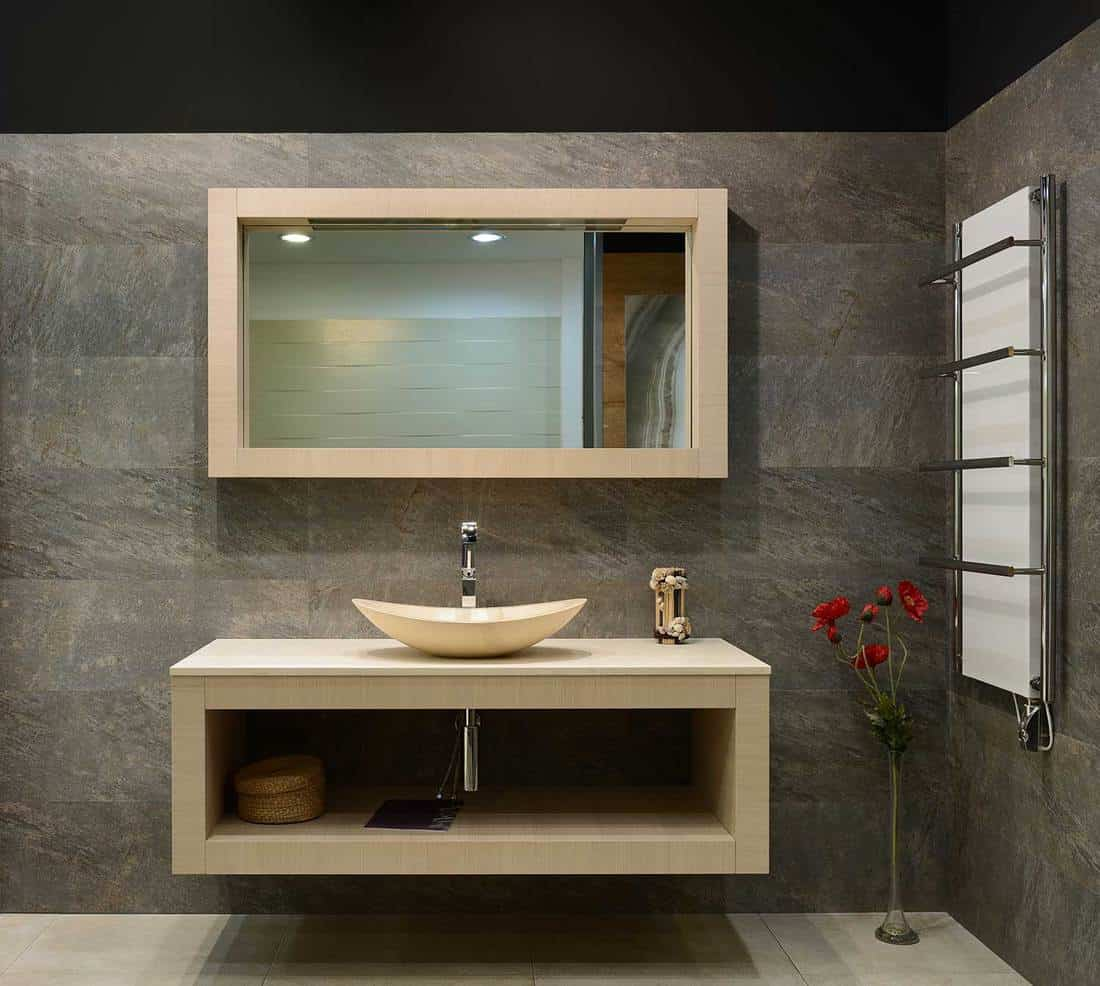 Modern bathroom interior with sink and rectangle mirror with wooden frame