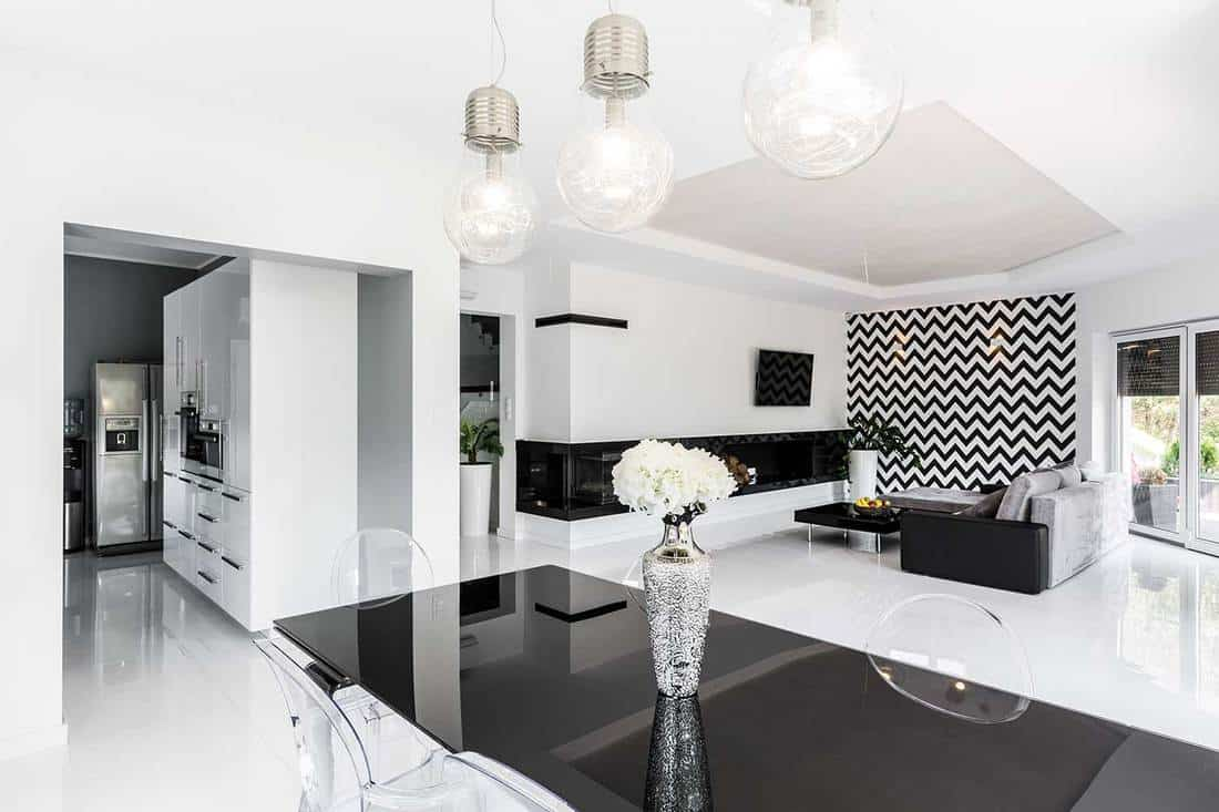 Modern black and white home living room design and dining table with view of the kitchen