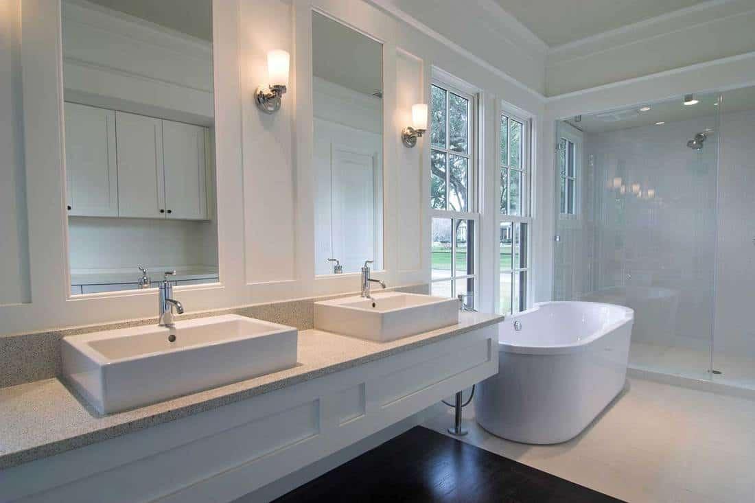 Modern clean white bathroom, elegantly designed with white bathtub