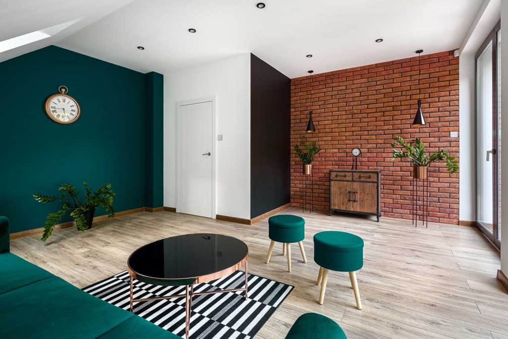 Modern designed living room with brick wall and amazing emerald green wall and furniture