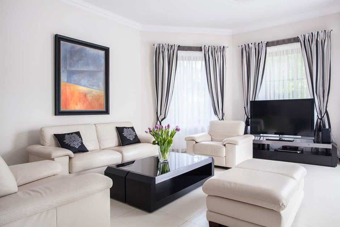 Modern designed living room with white sofa set, black coffee table and tile floor