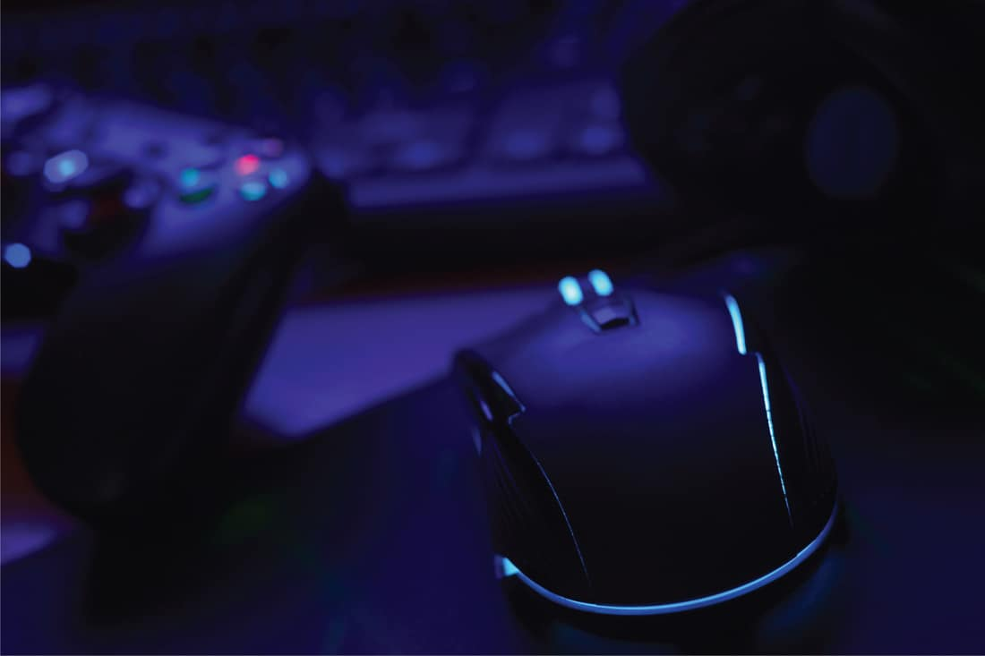 Modern gamepad and gaming mouse lies with keyboard and headphones on table in dark playroom scene