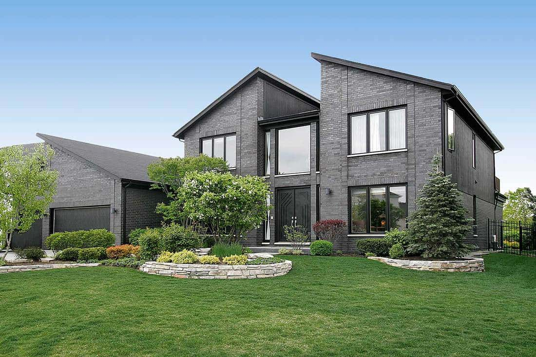 Modern gray brick home with front yard