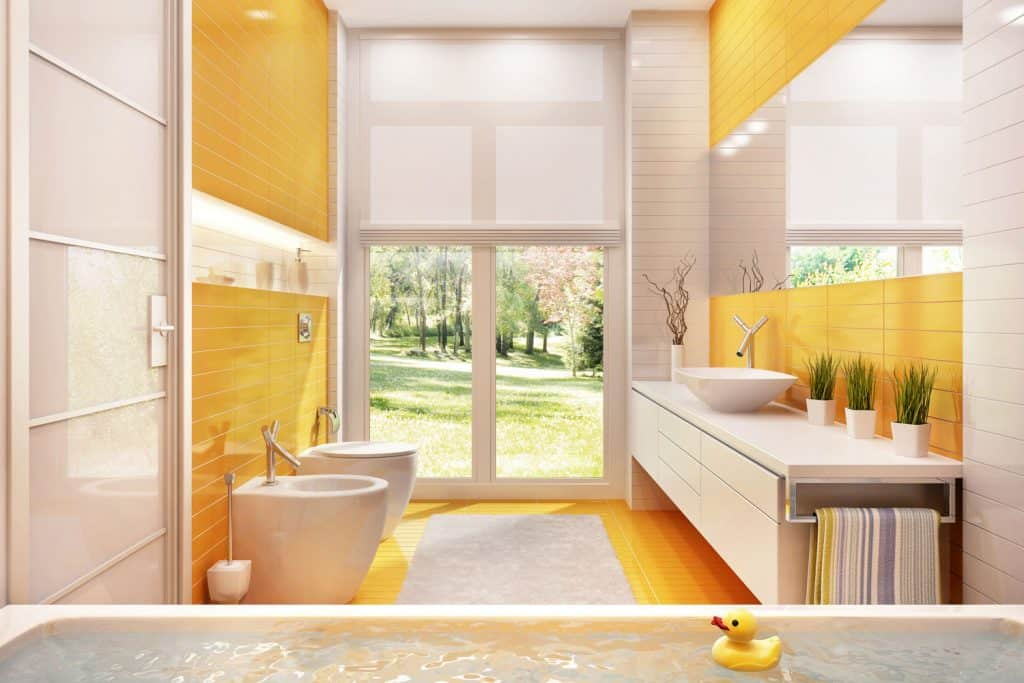Modern interior of a contemporary bathroom with orange decorative accent walls, a white vanity section with indoor plants, and a huge mirror on the side wall