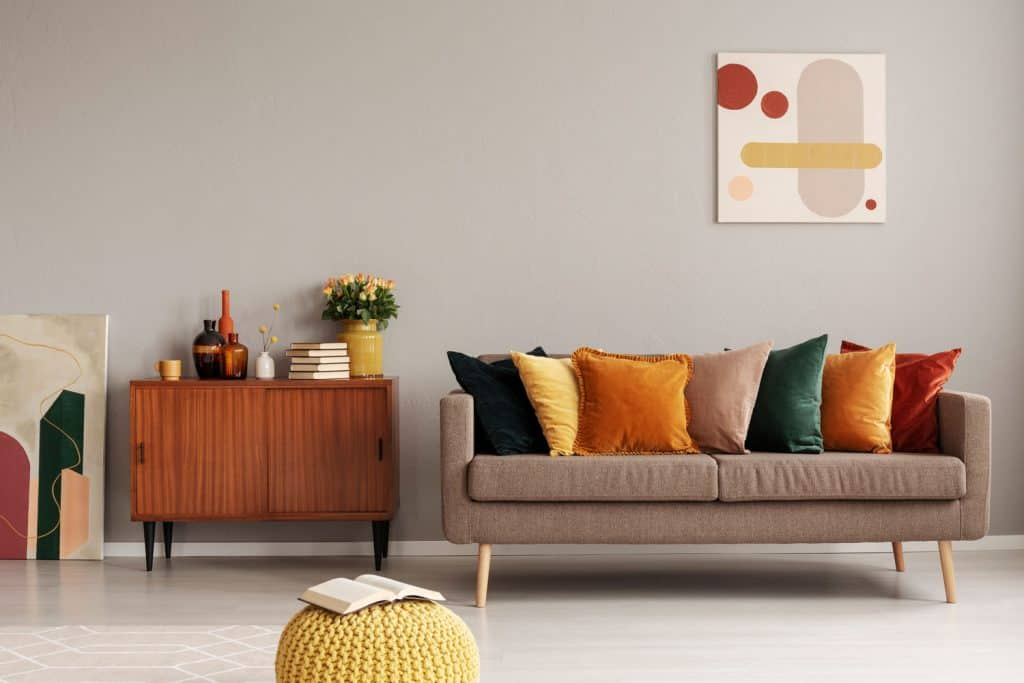 Modern interior of a retro themed living room with a brown fabric sofa with different colored throw pillows