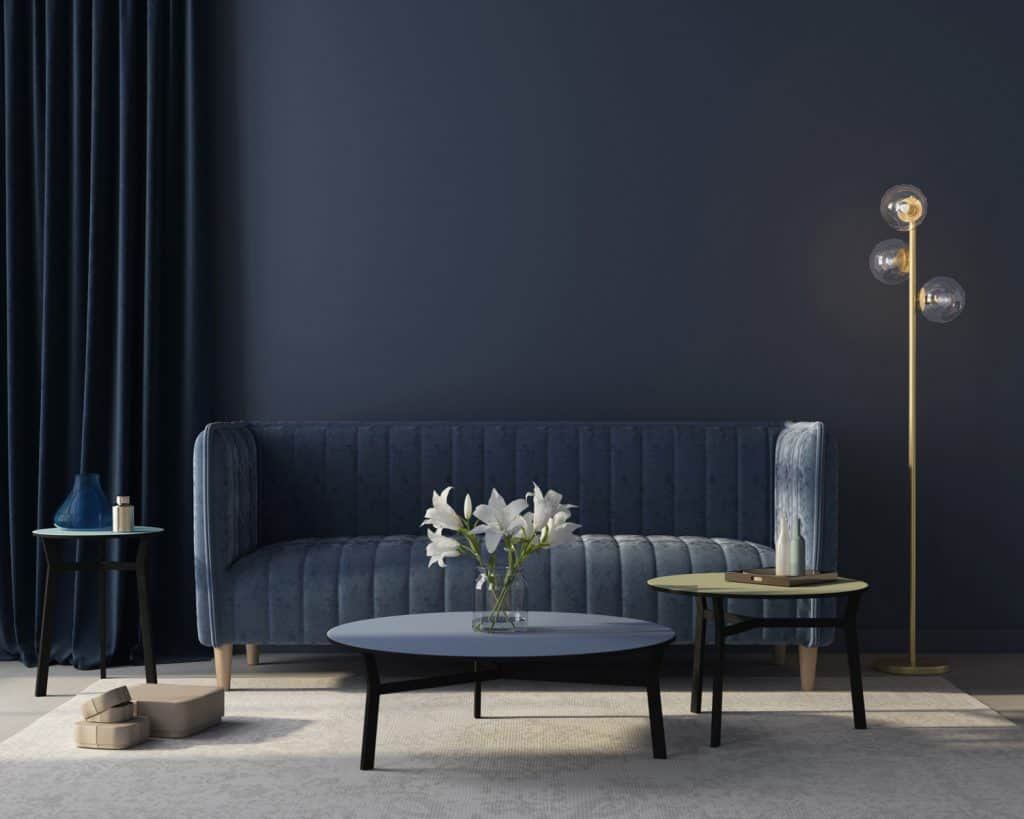 Modern interior of the living room in monochrome blue with a stylish velvet blue sofa, a beige carpet, a golden floor lamp