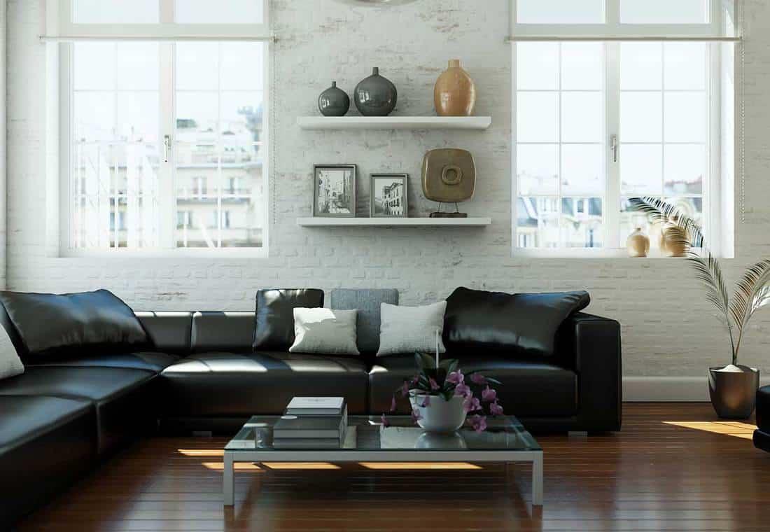 Modern living room interior design with L-shaped black sofa and hardwood floor