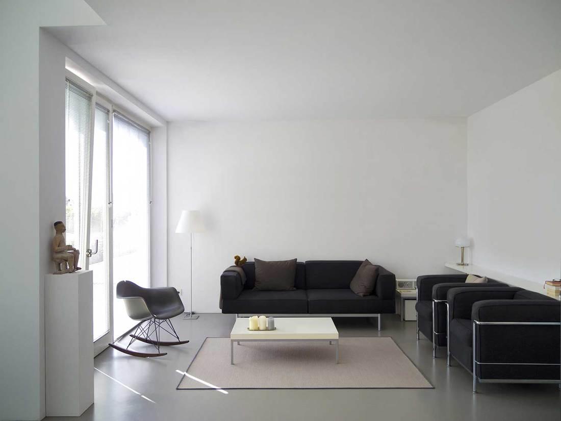 Modern living room interior with glass sliding door and black sofa set