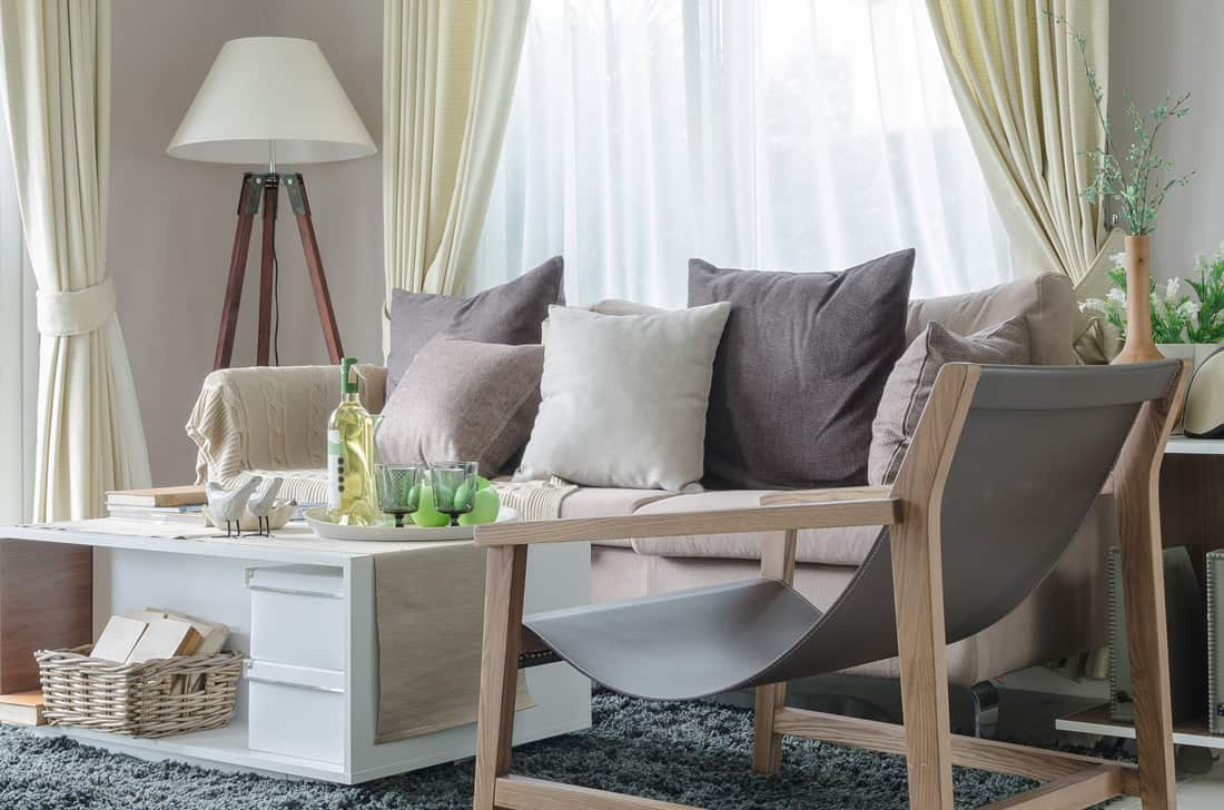 Modern living room with a unique accent chair, sofa and white lamp