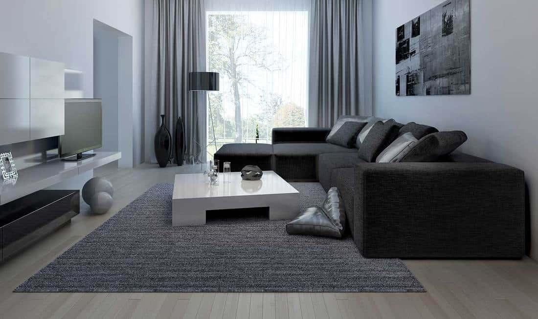 Modern living room with black corner sofa, carpet on wooden floor and artwork on wall