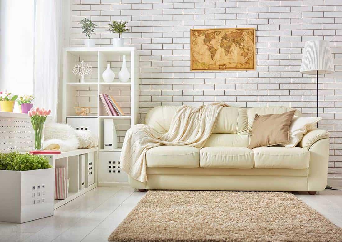 Modern living room with comfortable sofa, floor lamp and brick wall