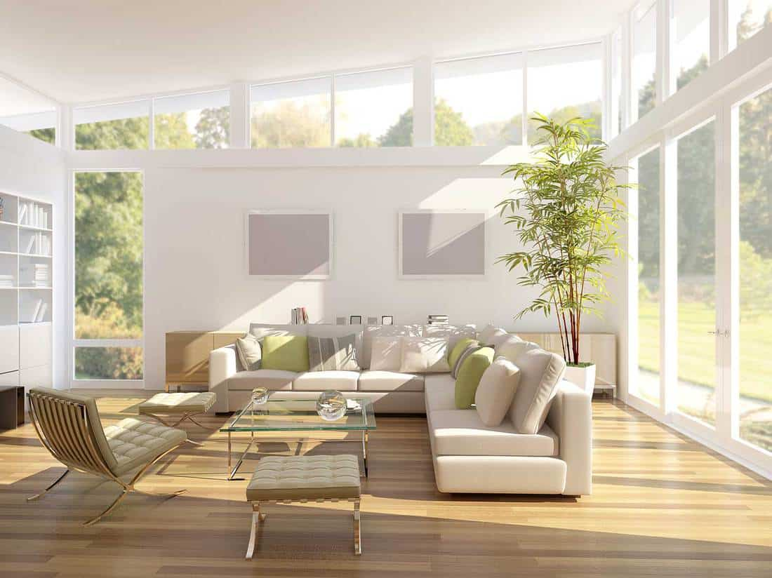 Modern living room with white L shape sofa, large glass doors and windows