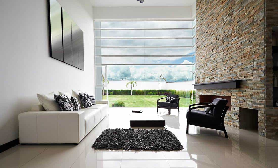 Modern living room with white sofa, black accent chairs, small rug and tile floor