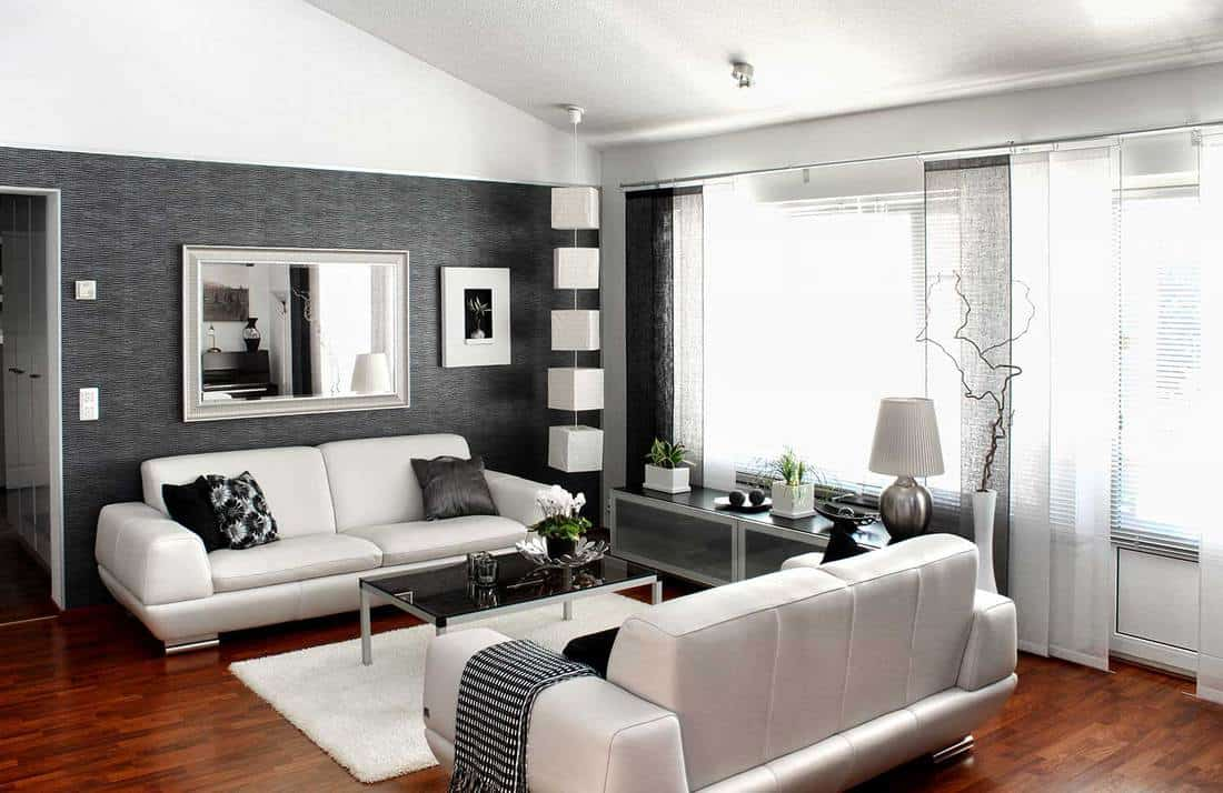 Modern living room with white sofas, mirror, white carpet rug and wooden floor