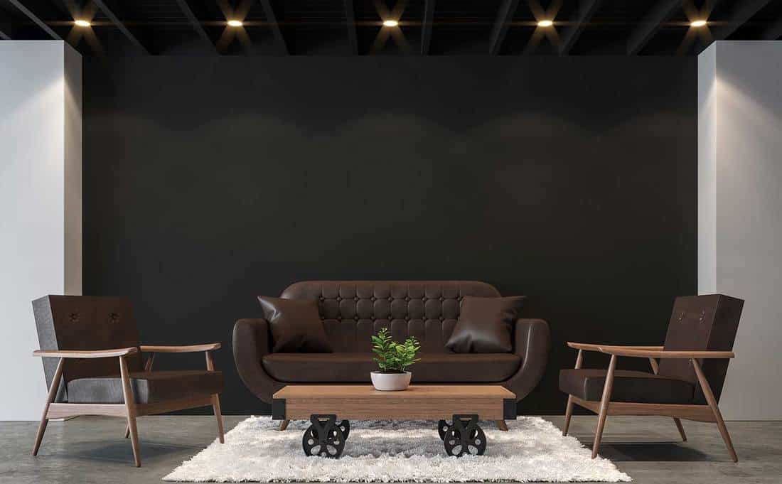 Modern loft living room with polished concrete floor, black wall and black wood ceiling furnished with brown leather furniture
