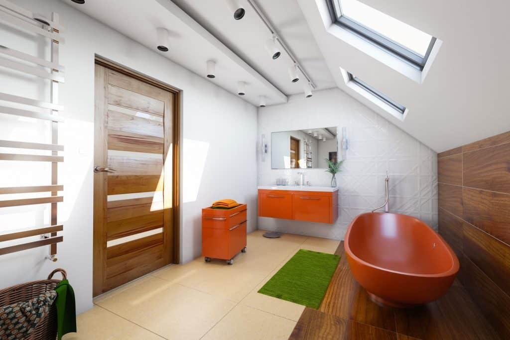Modern spacious bathroom with a hardwood door, orange bathtub and cabinets, and a sunroof window