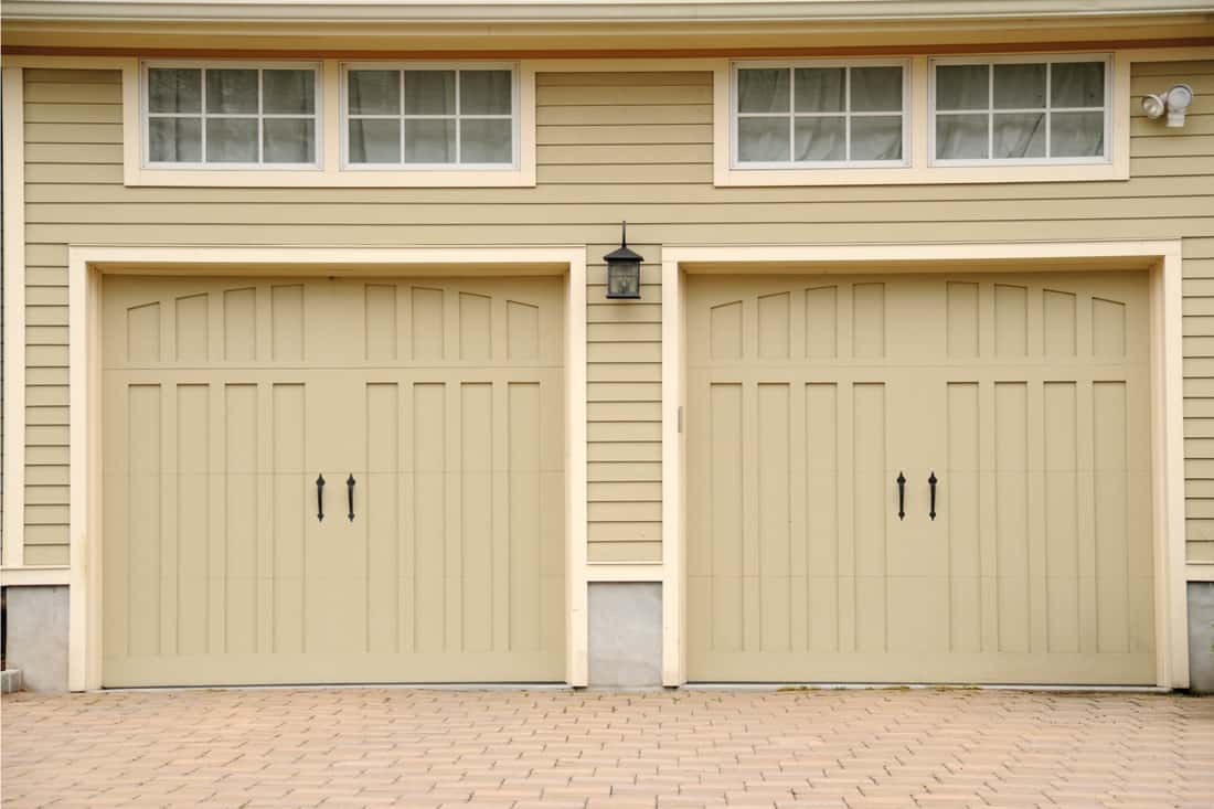 Modern two car garage with beige colored doors, full frame with paved driveway