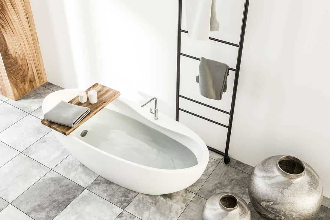 Modern white and wooden wall bathroom interior with gray marble floor, a white bathtub and towel rack