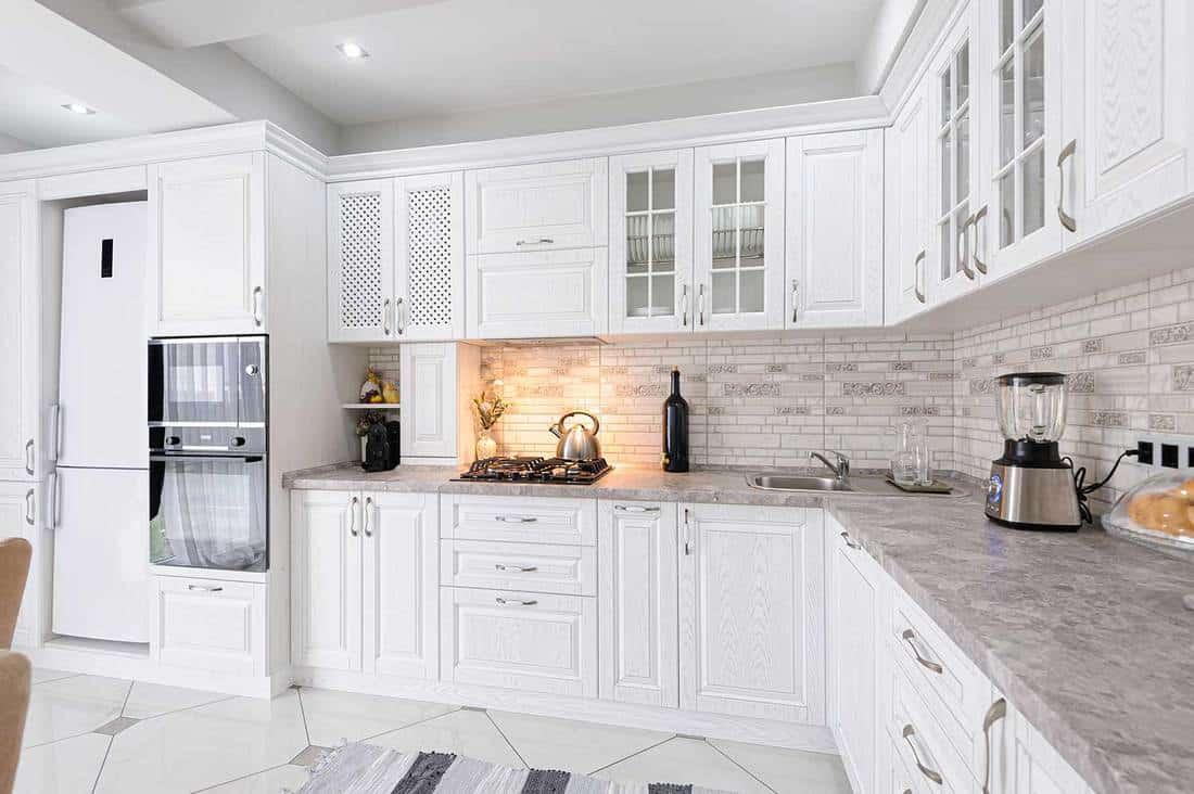 Modern white wooden kitchen interior with tiled floor