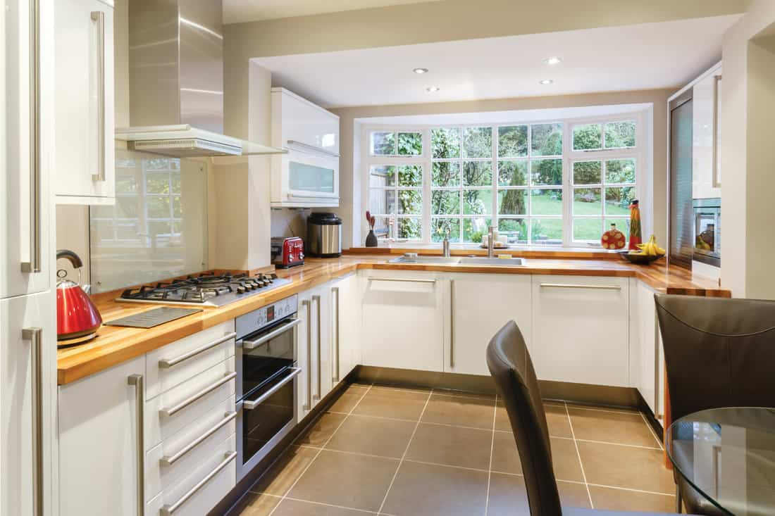 Modular modern kitchen interior with white units and contemporary dining area with brown floor
