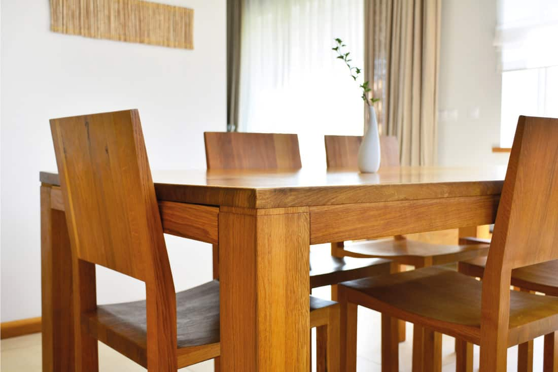 Natural oak wood dining table and chairs in neutral modern interior design house