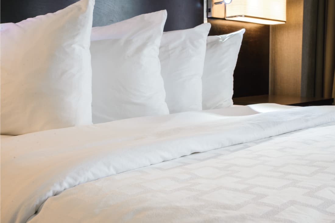 Neatly made hotel bed with 4 pillows