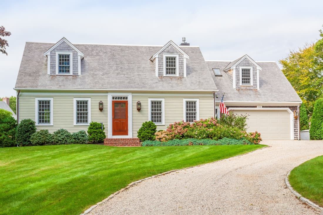 New England House with Beige Clapboard Exterior, Grey Shingle Roof, Gravel Driveway, Garage, Red Door, American Flag and Landscaped front yard with green grass, bushes and flowers.