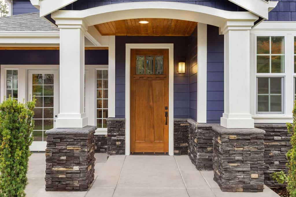 New luxury home exterior patio and front door with arch and columns