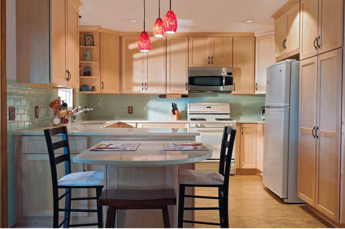 Newly remodeled kitchen interior with cork floors maple cabinets and glass tile backsplash