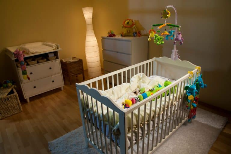 Nursery illuminated by lamp and decorated with modern furniture and many soft baby toys, What Color Night Light Is Best For Babies?