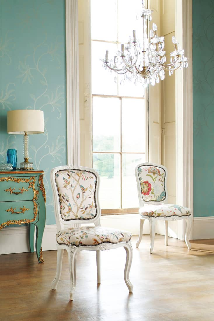 Old fashioned chairs on hardwood floor in room with big window
