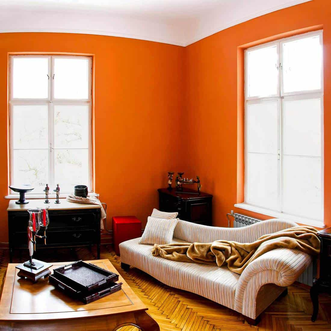 Orange room living room with parquet floor, sofa and wooden coffee table