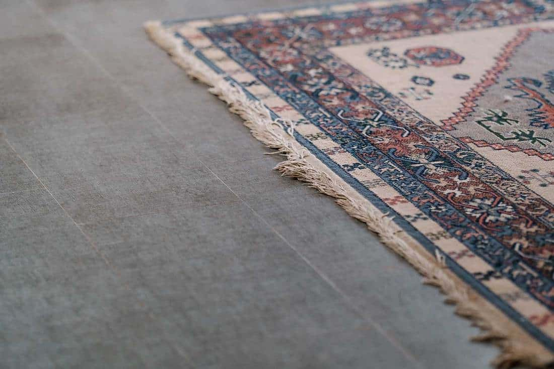 Ornamental design carpet on gray tile floor