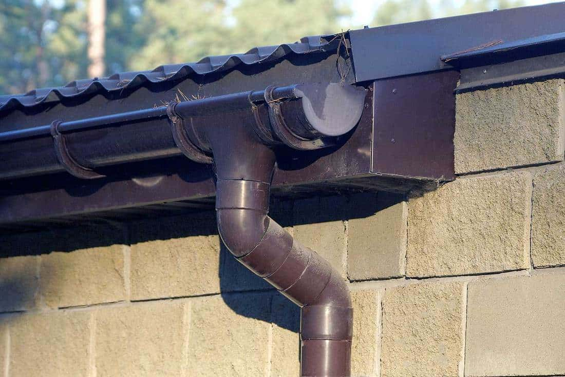 Part of brown plastic drain pipe under the roof of a house