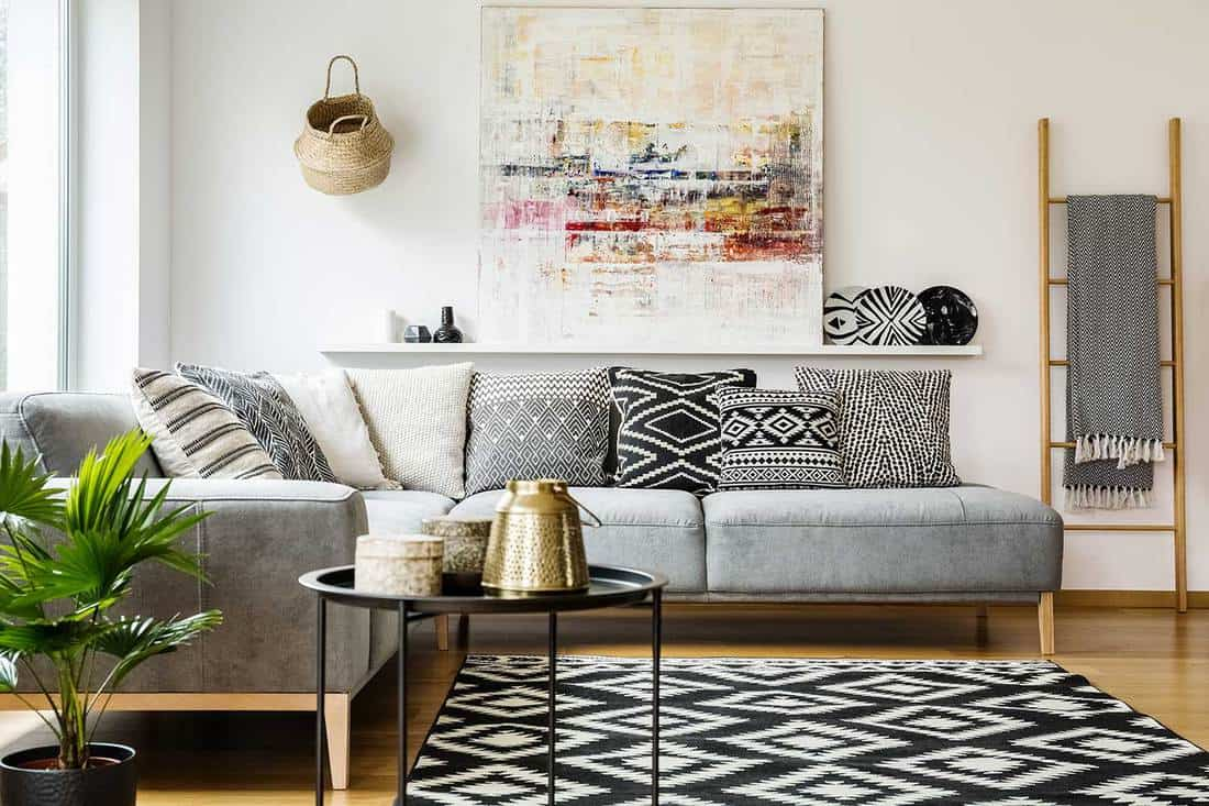 Patterned pillows on gray corner sofa in living room interior with table and painting