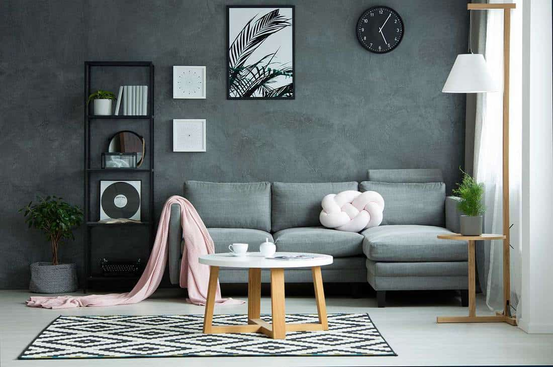 Pink blanket on sofa and round table on patterned rug in gray living room interior with poster on the wall