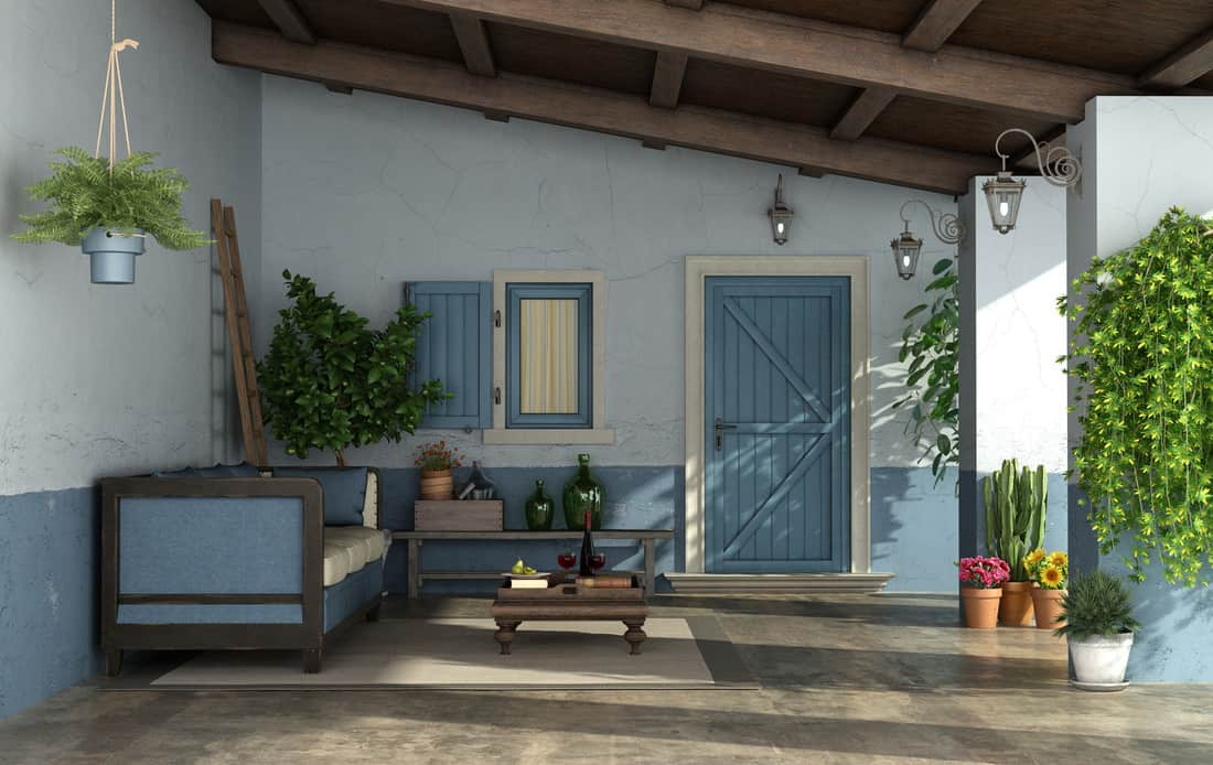 Porch in mediterranean style with front door, ,vintage sofa and old walls, front door design with coordinating furniture