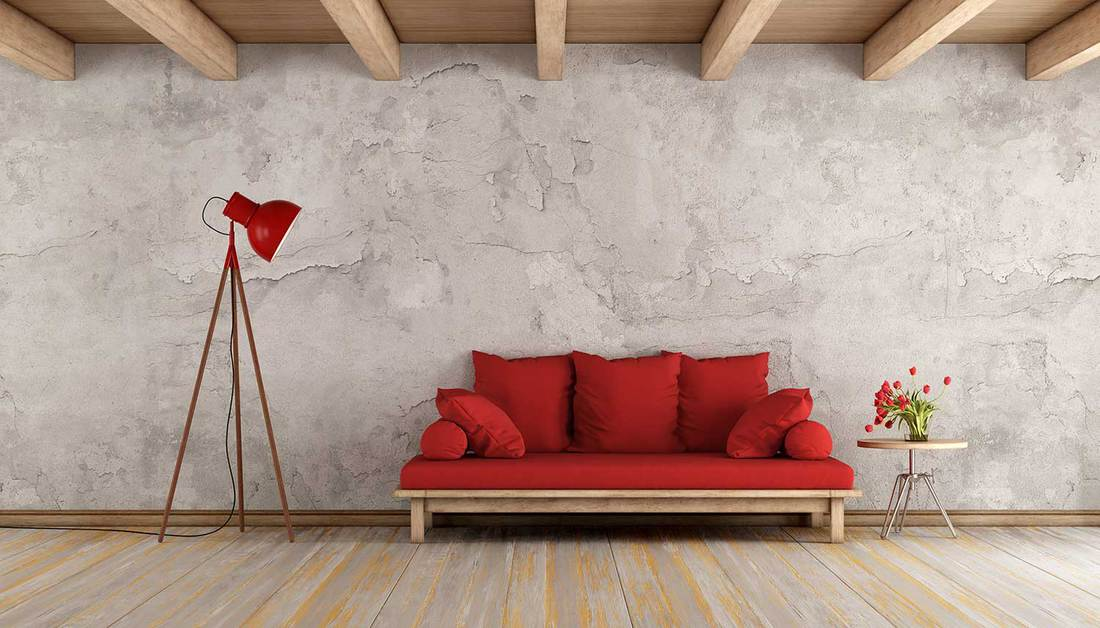 Red sofa in a grunge room with old wall and wooden ceiling